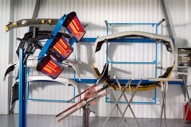 Schilderen en drogen onder lampen in professionele doos met carrosseriedelen na aanbrengen van stopverf en verf op bumper