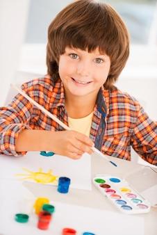 Schilderen is leuk. bovenaanzicht van kleine jongen die ontspant tijdens het schilderen met aquarellen aan tafel