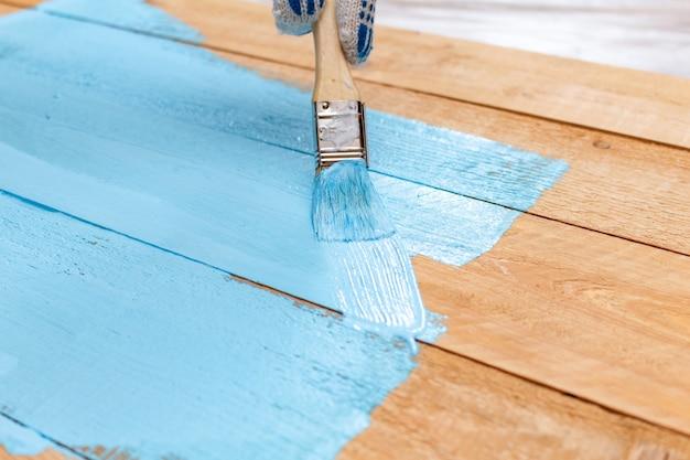 Schilderen met de verfkwast blauwe verf op het groene verfbakje op de houten doe-het-zelf