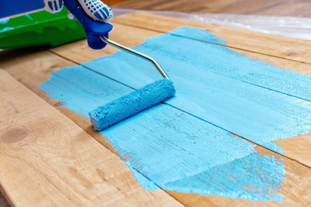 Schilderen met de verfroller blauwe kleur verf op de groene verfbak op de houten diy