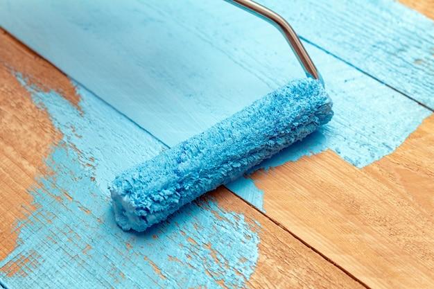 Schilderen met de verfroller blauwe kleur verf op de houten doe-het-zelf