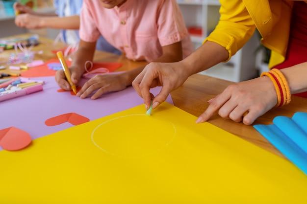 Schilderende cirkel. leraar van de basisschool helpt haar leerlingen bij het schilderen van een cirkel op geel papier