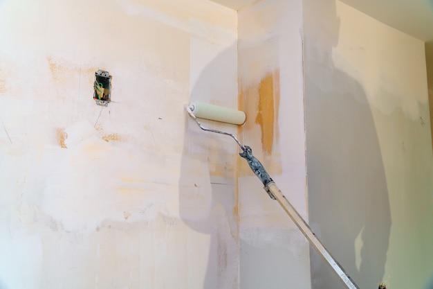Schilderende muren, fabrieksarbeider die rol voor het schilderen gebruikt