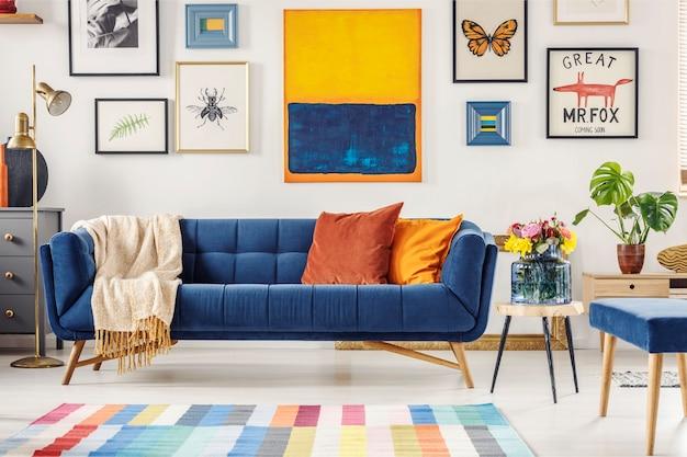 Schilderij boven marineblauwe bank in artistiek woonkamerinterieur met kleurrijk tapijt. echte foto