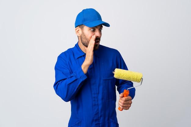Schildermens die een verfrol houden die op witte muur wordt geïsoleerd die iets met verrassingsgebaar fluistert terwijl het kijken aan de kant