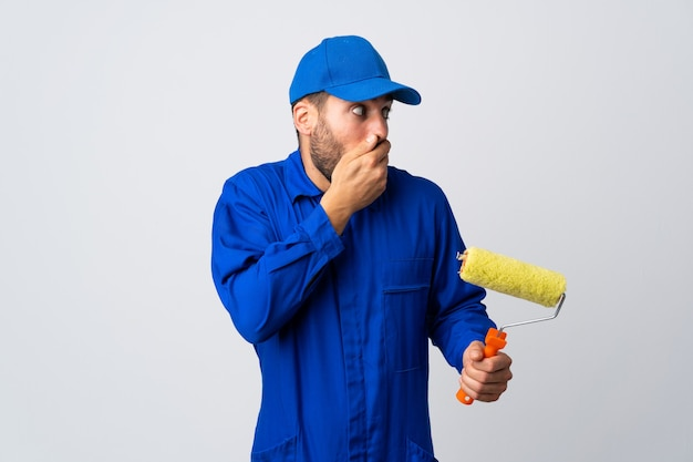 Schildermens die een verfroller houdt die op wit wordt geïsoleerd dat mond behandelt en naar de kant kijkt