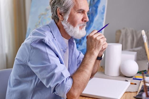 Schildermens die voor hobby schildert, hij zit thuis na te denken, in contemplatie