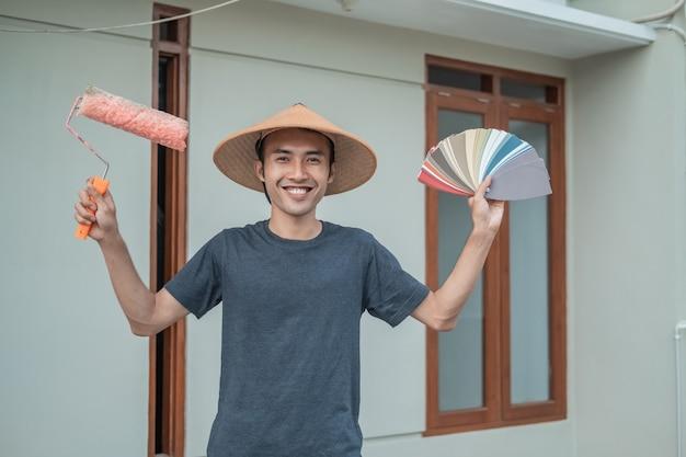 Schilders dragen petten met opgeheven handen die verfrollers en voorbeeldverfkleuren vasthouden