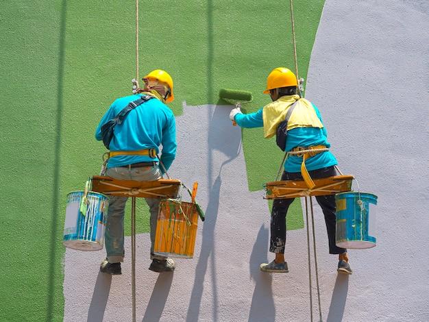 Schilders schilderen buitenkant van het gebouw