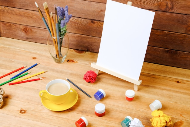 Schildersezel, kunstborstels en koffie op een houten tafel. werkplek van de kunstenaar. creativiteit en hobby concept.