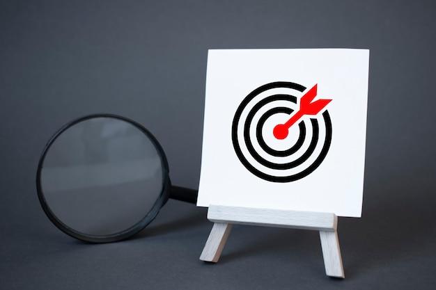 Schildersezel, vergrootglas en pijl in het doelcentrum. concept van succes, groei en prestatieverbetering. statistieken en bedrijfsanalyses. inkomen inkomsten