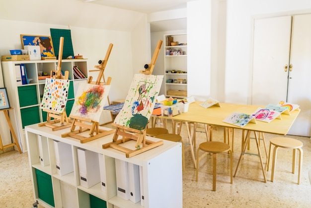 Schildersezels met waterverfschilderijen die door kinderen in kunstklasse worden gemaakt.