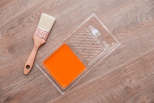 Schilderskuvet met oranje verf op houten bruine vloer