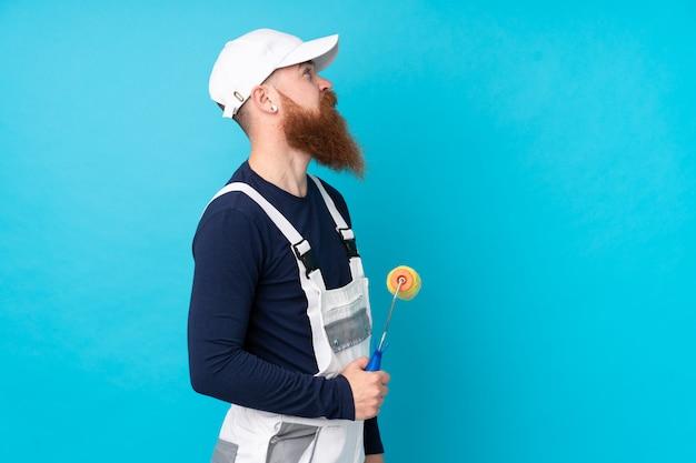 Schildersmens die met lange baard over geïsoleerde blauwe muur aan de kant kijken