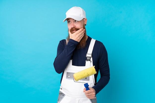 Schildersmens die met lange baard over geïsoleerde blauwe muur een idee denken