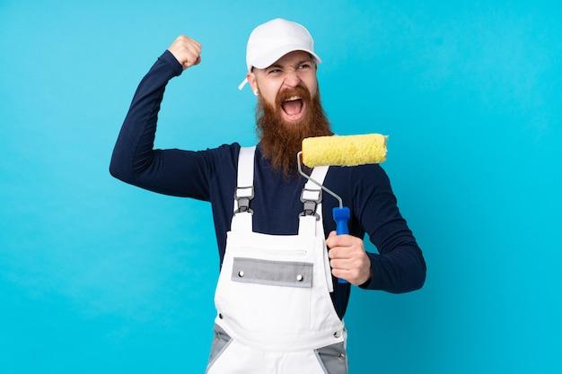 Schildersmens die met lange baard over geïsoleerde blauwe muur een overwinning vieren