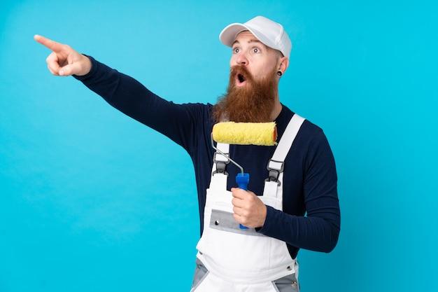 Schildersmens die met lange baard over geïsoleerde blauwe muur weg richten