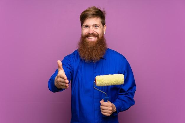 Schildersmens met lang baardhandenschudden na goede deal