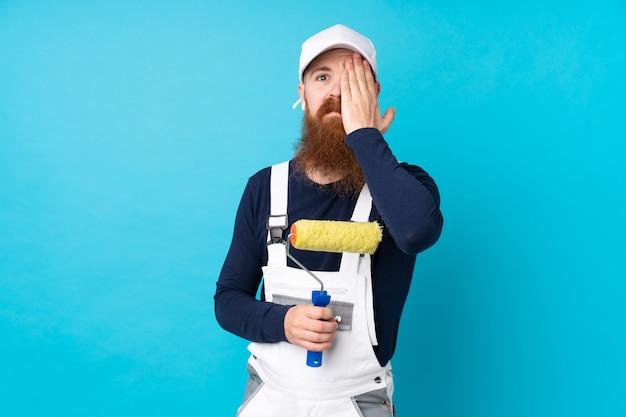 Schildersmens met lange baard over geïsoleerde blauwe muur die een oog met de hand behandelen