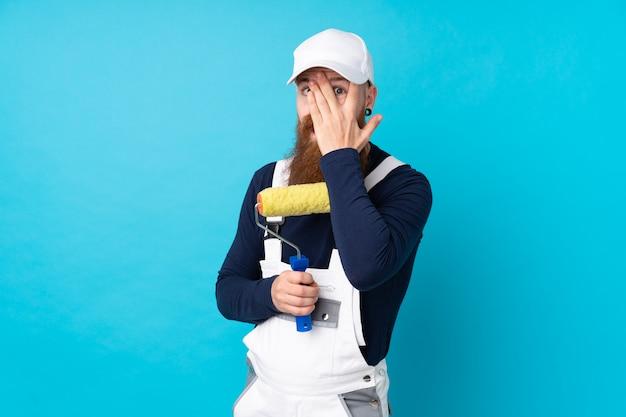 Schildersmens met lange baard over geïsoleerde blauwe muur die ogen behandelen en door vingers kijken