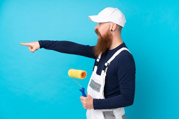 Schildersmens met lange baard over geïsoleerde blauwe muur die vinger aan de kant richten