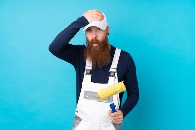 Schildersmens met lange baard over geïsoleerde blauwe muur met verrassingsgelaatsuitdrukking