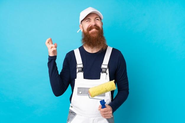 Schildersmens met lange baard over geïsoleerde blauwe muur met vingers kruising
