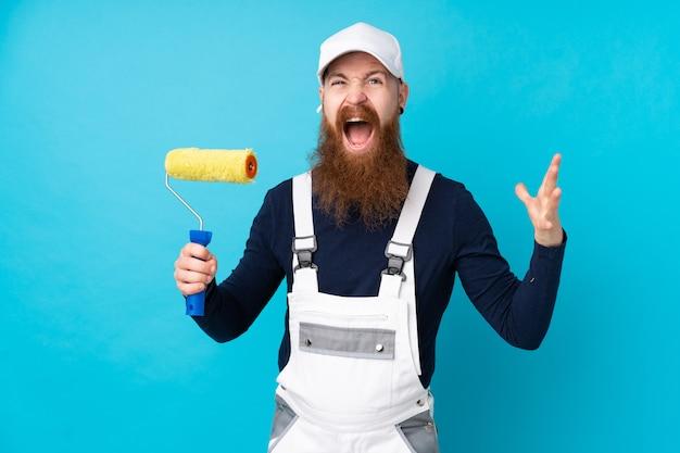 Schildersmens met lange baard over geïsoleerde blauwe muur ongelukkig en gefrustreerd met iets