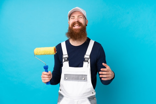 Schildersmens met lange baard over het geïsoleerde blauwe muur lachen