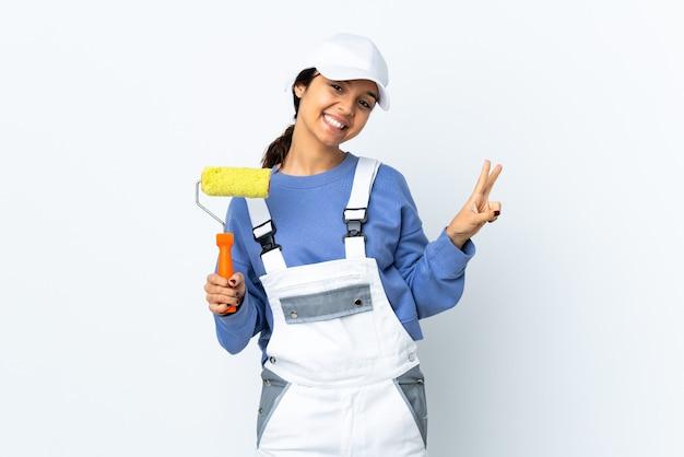 Schildersvrouw over geïsoleerde witte achtergrond die overwinningsteken met beide handen toont
