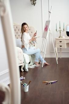 Schildertekening in kunststudio die schildersezel gebruiken. portret van een jonge vrouw die met olieverven op wit canvas, zijaanzichtportret schildert