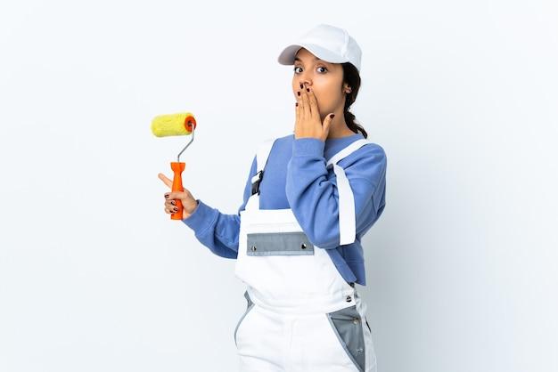 Schildervrouw over geïsoleerde witte muur met verrassingsuitdrukking terwijl zij kant wijst