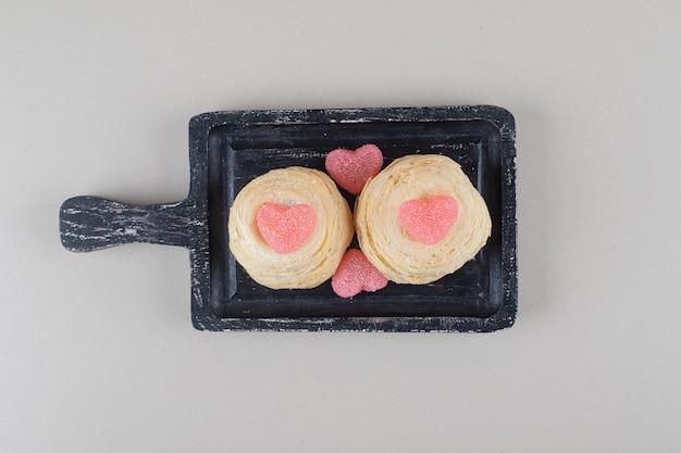 Schilferige cakes en hartmarmelades op een zwart dienblad op marmeren achtergrond.