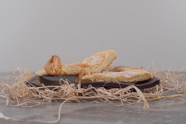 Schilferige flatbread op schotel op een stapel stro op marmer