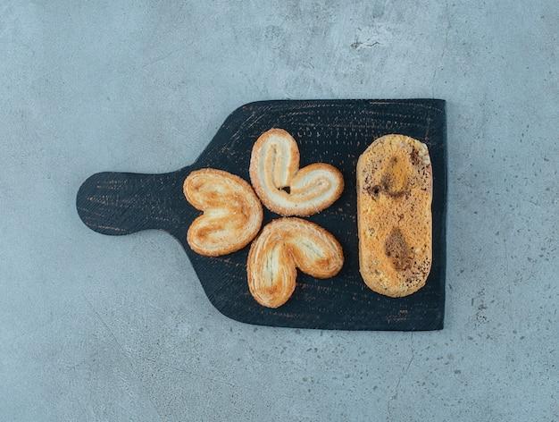 Schilferige koekjes en een kleine cake op een bord op marmeren achtergrond. hoge kwaliteit foto