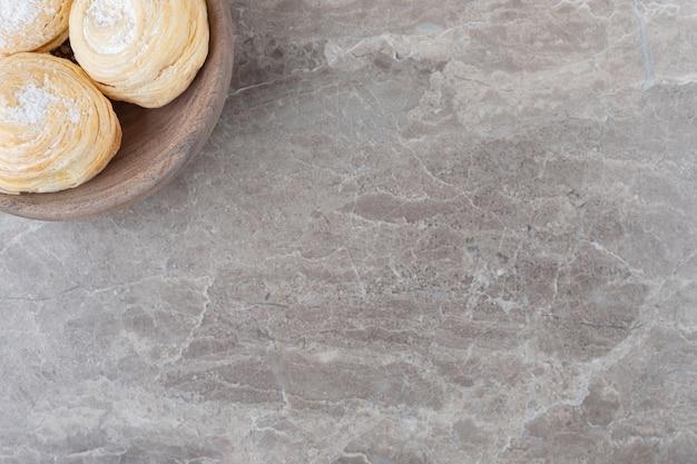 Schilferige koekjes in een kleine kom op marmeren oppervlak