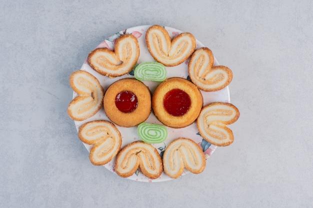 Schilferige koekjes, marmelades en met gelei gevulde cakes op een schaal op marmeren tafel.