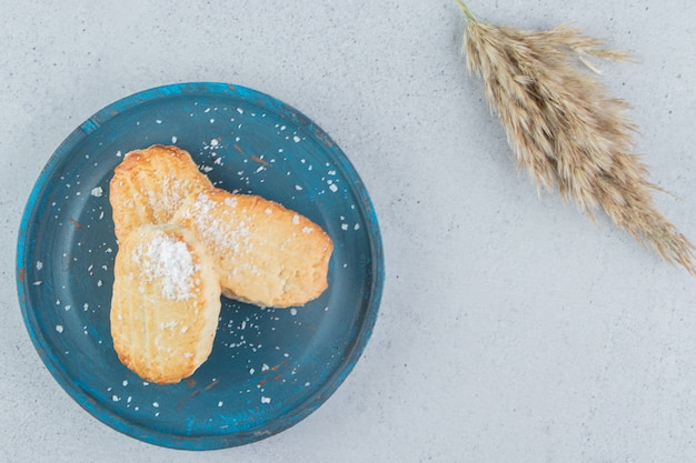 Schilferige koekjes op een blauwe schotel naast een steel van verengras op marmeren achtergrond.