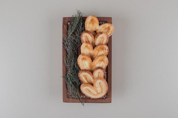 Schilferige koekjes opgesteld op een klein houten dienblad met een bundel van dennenbladeren op marmeren achtergrond.