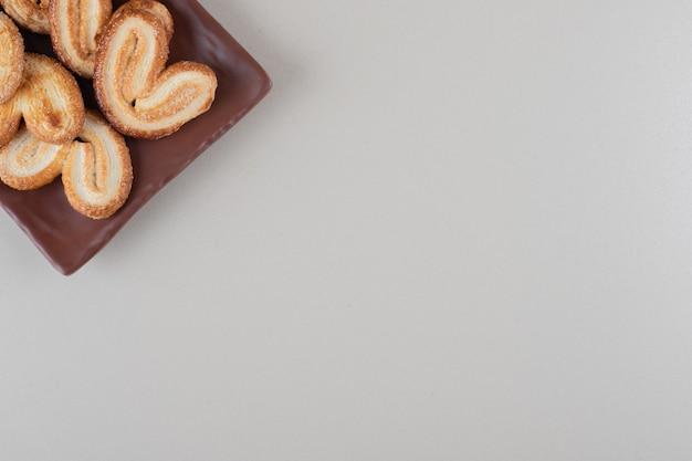 Schilferige koekjesbundel op een schotel op witte achtergrond.