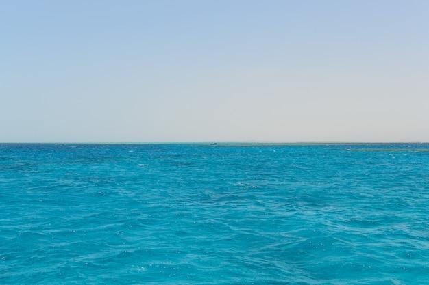 Schip aan de horizon van de blauwe zee
