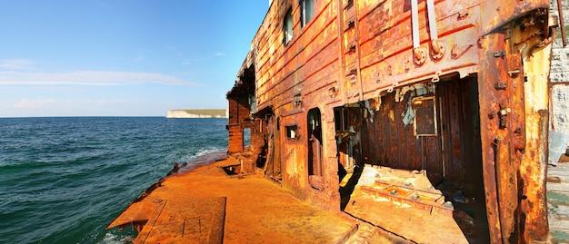 Schipbreuk. roestig vrachtschip in de buurt van de bergkust