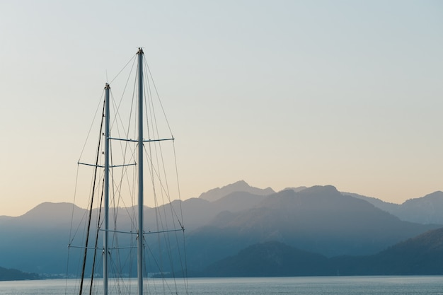 Schipmast op blauwe zonsonderganghemel en bergen.