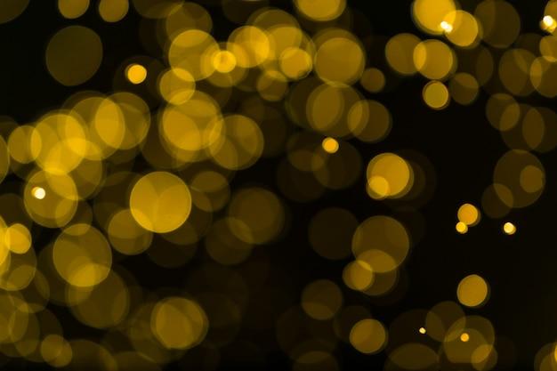 Schitter vintage lichtenachtergrond. donker goud en zwart. defocused