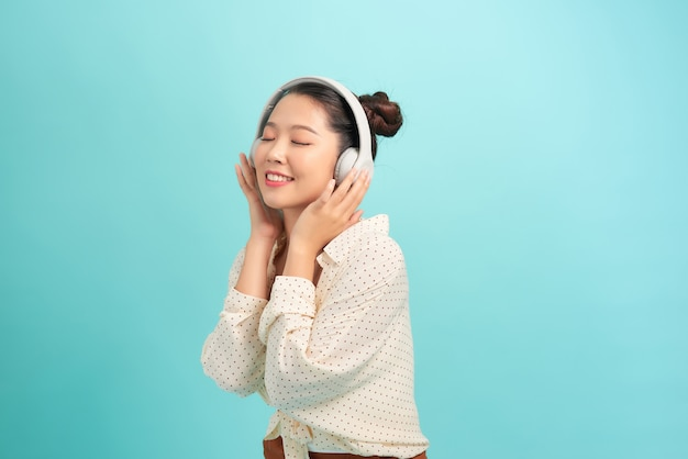 Schitterend aziatisch meisje luisteren muziek in hoofdtelefoons