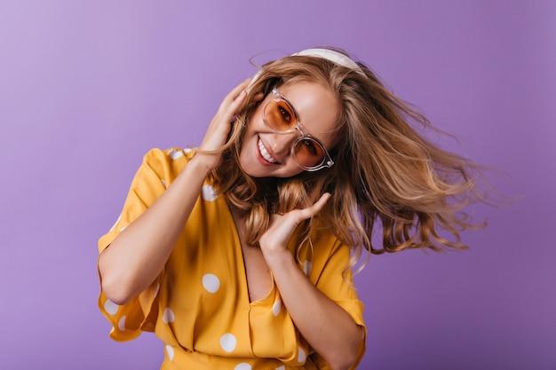 Schitterend blond meisje dansen met een glimlach. portret van vrolijke gelooide vrouw in hoofdtelefoons.