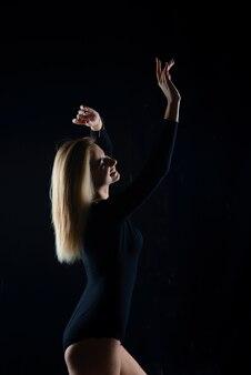 Schitterend blond model met perfect figuur poseren in een zwarte bodysuit.