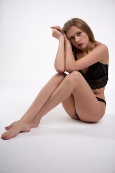 Schitterend blondemeisje in zwarte kanten ondergoedzitting