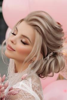 Schitterend blondemeisje met roze luchtballons.