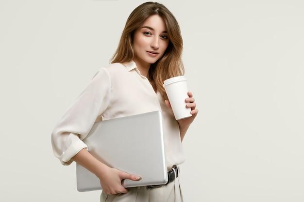 Schitterend donkerbruin model in witte kleren met laptop en koffie